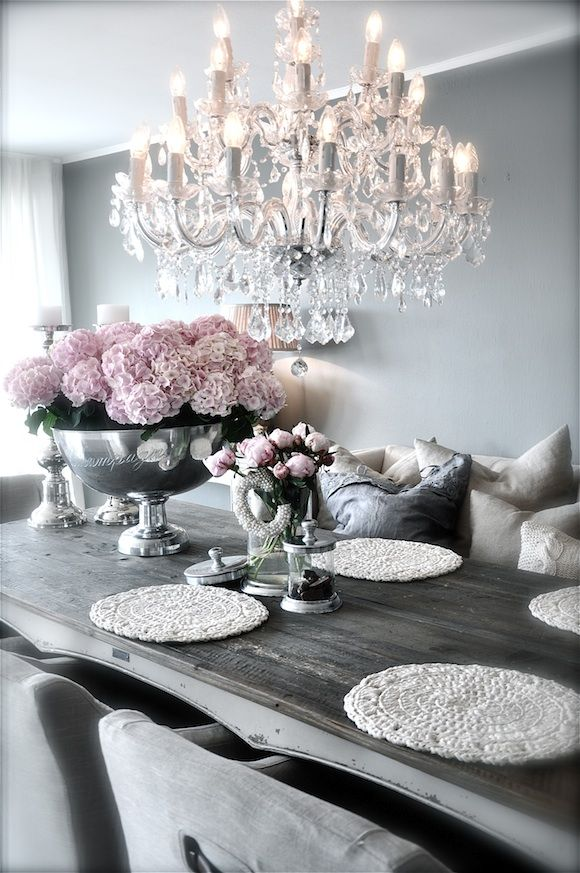 Grey dining room with chandelier and pink flowers